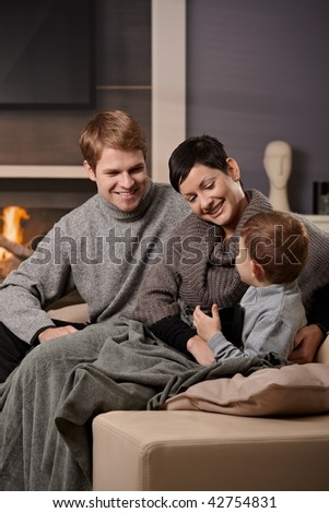 Happy family sitting on sofa at home in front of fireplace, smiling.
