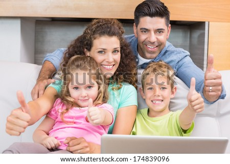 Happy family sitting on sofa using laptop giving thumbs up at home in living room