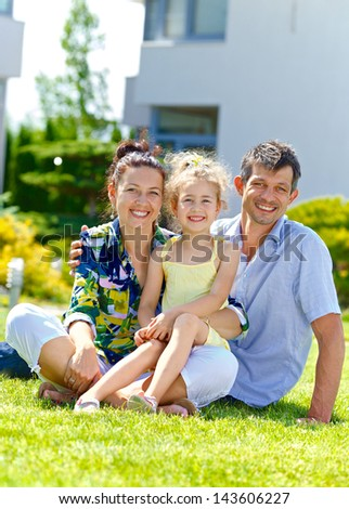 Happy family sitting on the lawn in front of his new cottage