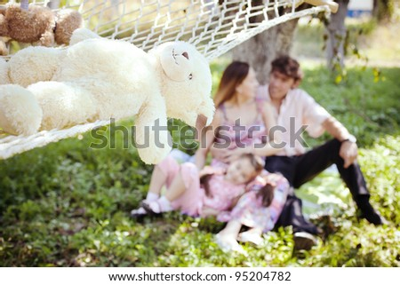 happy family sitting on the lawn in the apple garden next to the hammock