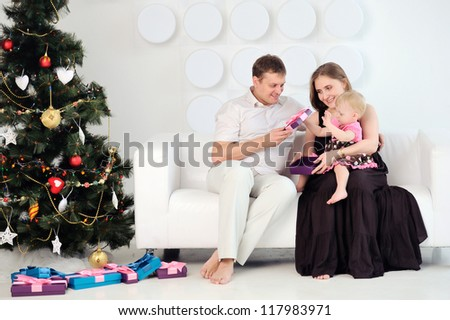 Happy family sitting on the sofa. Baby mom in her arms. Parents are a child. Christmas decorations. White background. The floor boxes with gifts.