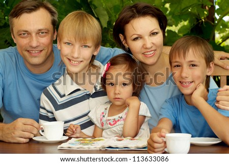 Happy family sitting on the veranda of his cottage