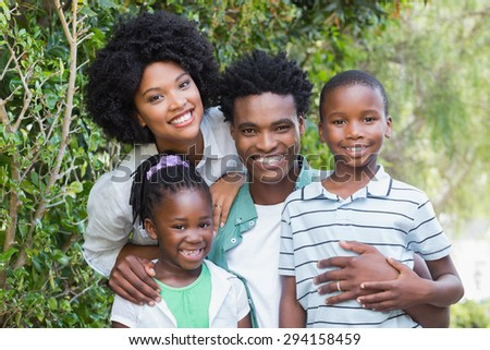 Happy family smiling at camera in the garden at home