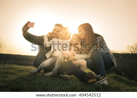 Happy family smiling while taking self-portrait  in park. #604542512