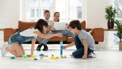 Happy family spend leisure time in living room young parents relax on sofa with laptop, two kids children playing with wooden blocks on warm floor in comfy modern living room with underfloor heating