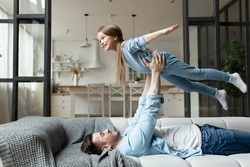 Happy family spend time together in living room father lying on couch lifts up little daughter, kid girl looking like plane imagines herself flying in air. Funny activities on weekend at home concept