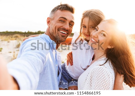 Happy family spending good time at the beach together, taking selfie