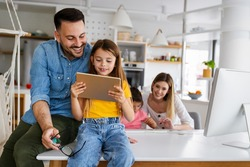 Happy family spending time at home and using digital, technology devices.