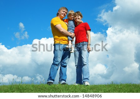happy family stand on green grass under sky with clouds