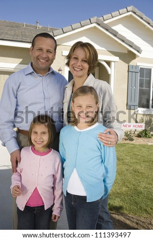 Happy family standing in front of new house