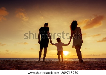 Happy family standing on the background of the sunset sky and sea holding hands