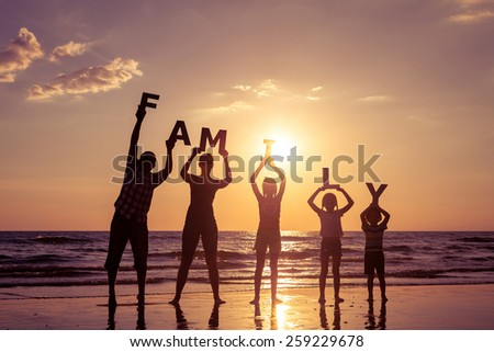 Happy family standing on the beach at the sunset time. They keep the letters forming the word \