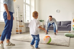 Happy family staying at home, having fun together and engaging their small child in sport games. Young dad with little son playing football with inflatable ball in living-room