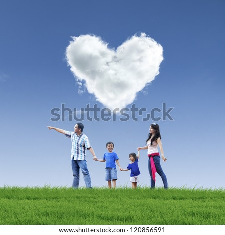 Happy family taking a stroll in the park under love shaped cloud