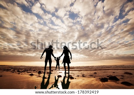 Happy Family Together Hand In Hand On The Beach At Sunset, Summer Time. Mother, Father And A Little Child