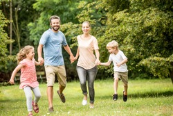 Happy family together in summer runing in the nature