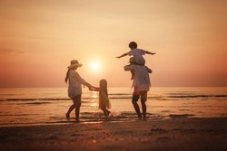Happy family travel on beach in holiday, outdoor activity on summer vacations. Silhouette of a happy family enjoying the evening play on the beach.