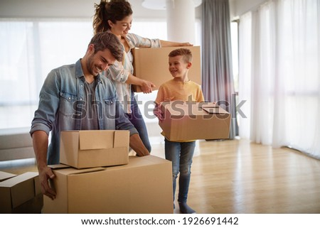 Happy family unpacking boxes in new home on moving day Foto stock ©