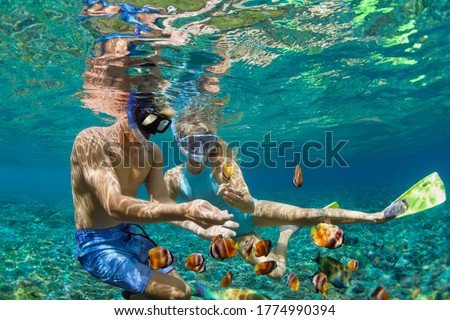 Happy family vacation. Young couple in snorkeling mask hold hand, dive underwater with fishes in coral reef sea pool. Travel lifestyle, watersport adventure, swim activity on summer beach holiday Stockfoto ©