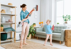 Happy family vacuuming the room. Mother and daughter doing the cleaning in the house.