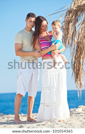 happy family walking along the beach while on vacation
