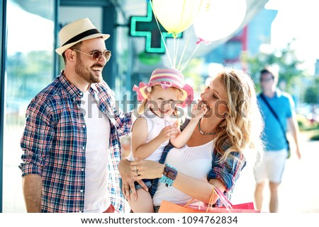 Happy family walking along the shopping mall with shopping bags and balloons. #1094762834