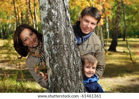 Happy family walking at the autumn park.