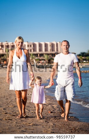Happy family walking at the beach. Summer vacations - stock photo