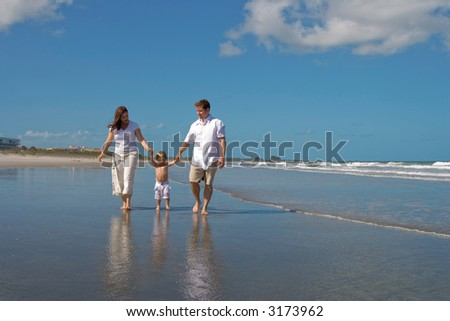 Happy family walking on a beach