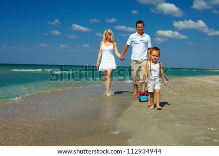 happy family walking on sea beach, vacation