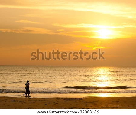 Happy family walking on the beach at sunrise for holiday time