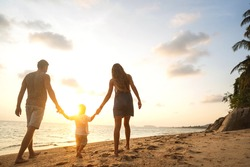 happy family walking on the beach at sunset