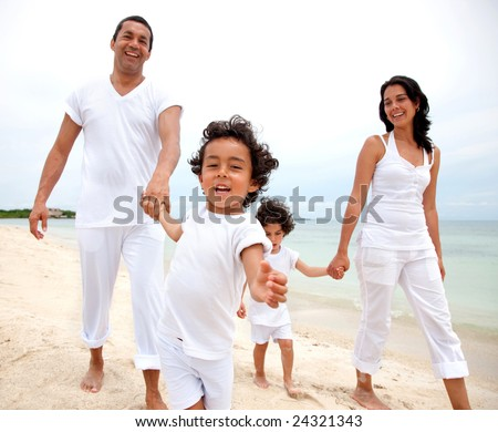 Happy family walking on the beach - togetherness concept
