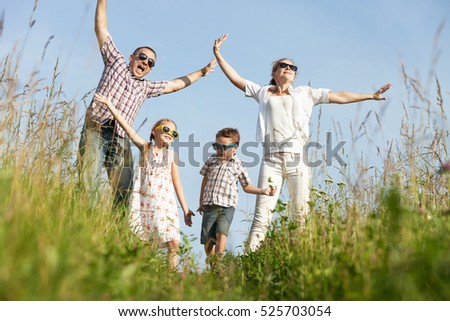 Happy family walking on the field at the day time. People having fun on the park. Concept of friendship forever and of summer vacation.
