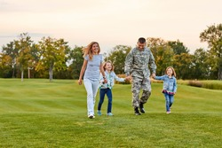 Happy family walking on the grass. Soldier with his wife and daughters in the park.
