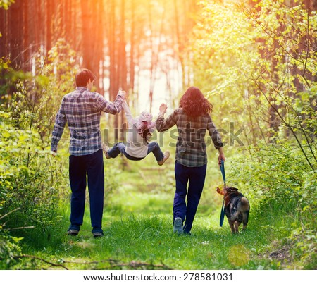 happy family walking with dog...
