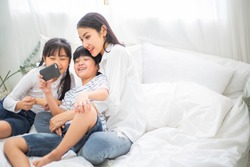 Happy family watch movie on smartphone. mother cuddle son and daughter video chat with friend or family for social distancing. stay home during Coronavirus or COVID19. new normal lifestyle insurance