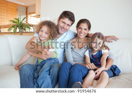 Happy family watching TV together in their living room