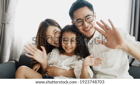 Happy family waving hand greeting to camera. Asian family daughter, father and mother smiling in front of camera during live streaming in social network. Family picture waving hand and smiling happily