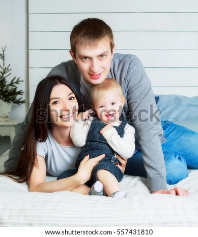 happy family with a baby at home in bed