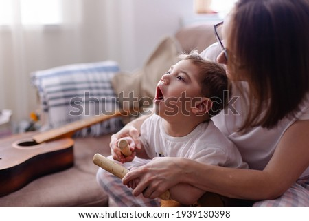 Happy family with a child with cerebral palsy. The mother and her disabled son lead a normal life. Leisure time together. Child development games at home. Wooden musical instruments. Rehabilitation  Stock photo ©