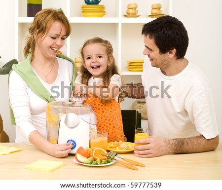 Happy family with a kid making fresh fruit juice from oranges - healthy diet concept
