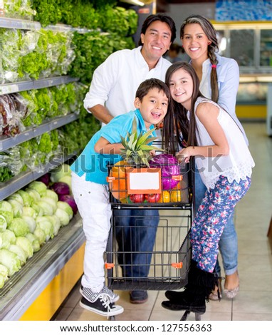 Happy family with a shopping trolley at the supermarket