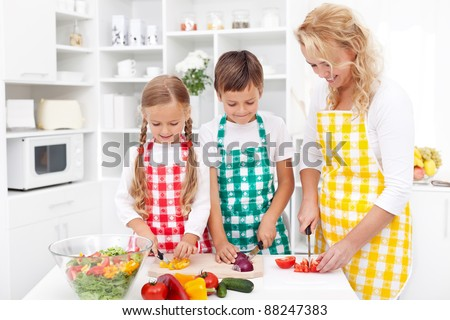Happy family with aprons preparing healthy fresh salad together