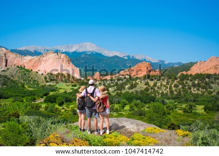 Happy family with arms around each other enjoying beautiful mountain view on  hiking trip. Beautiful red mountains and green hills in Colorado. Garden of the Gods, Colorado Springs, Colorado,  USA. #1047414742