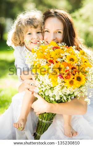 Happy family with big bouquet of spring flowers having fun outdoors against blurred green background. Mother`s day celebration concept
