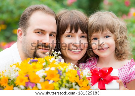Happy family with bouquet of flowers against green background. Spring holiday concept. Mother\'s day