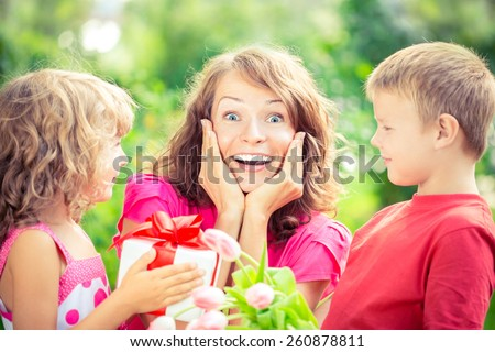 Happy family with bouquet of flowers and gifts outdoors. Young beautiful mother with son and daughter lying on green grass. Spring holiday concept. Mother\'s day. Surprise and joy
