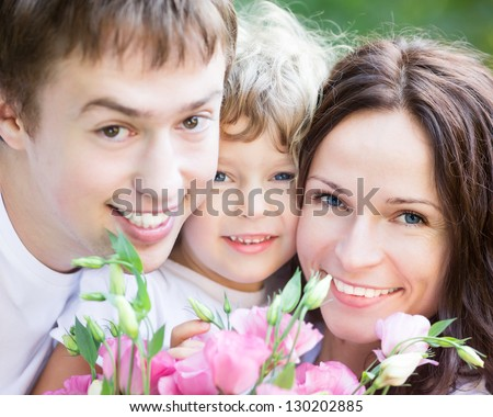 Happy family with bouquet of spring flowers having fun outdoors. Mothers day celebration concept