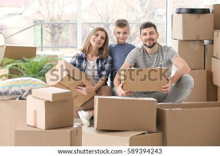Happy family with cardboard boxes. Moving concept #589394243